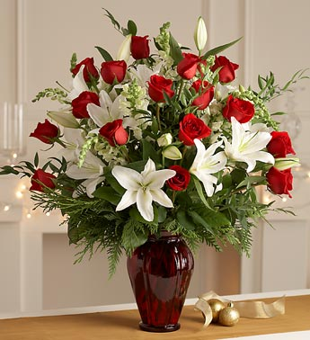 rose and lily christmas bouquet in red vase